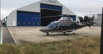 Apollo Air Services' helicopter by the hangar at Cambridge City Airport